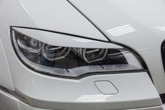 De koplamp met voeringsmening van stemmende auto van luxe de zeer dure nieuwe witte BMW X6 M Lumma CLR bevindt zich in de wasdoos royalty-vrije stock fotografie