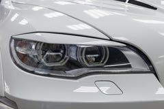 De koplamp met voeringsmening van stemmende auto van luxe de zeer dure nieuwe witte BMW X6 M Lumma CLR bevindt zich in de wasdoos stock afbeelding