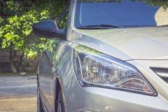De koplamp van de auto in dalingen van ochtenddauw op de achtergrond van bomen Stock Fotografie