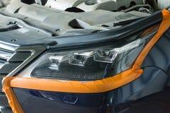 De koplamp van de auto is gelijmd langs de perimeter voor poetsmiddel royalty-vrije stock afbeeldingen