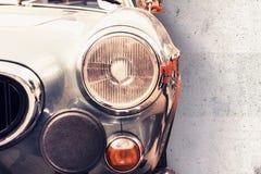 De koplamp van de oude mooie auto op de achtergrond van een concrete muur De ruimte van het exemplaar De reparatie van conceptenb royalty-vrije stock foto