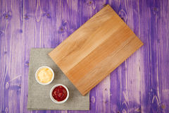 De koppen met ketchup en kaas op servet maakten van canvas op een houten lijst Royalty-vrije Stock Foto