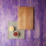 De koppen met ketchup en kaas op servet maakten van canvas op een houten lijst Stock Fotografie