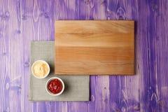 De koppen met ketchup en kaas op servet maakten van canvas op een houten lijst Stock Foto's