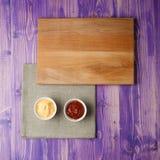 De koppen met ketchup en kaas op servet maakten van canvas op een houten lijst Stock Afbeelding
