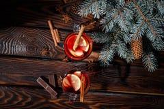 De koppen van citroenthee met kaneel en chocolade op een pijnboom vertakken zich en dienen achtergrond in Thee en chocolade Royalty-vrije Stock Afbeeldingen