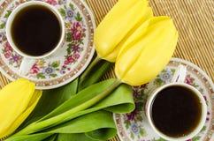 De koppen van de porseleinthee met gele tulpenbloemen Royalty-vrije Stock Fotografie
