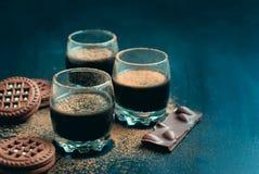 De koppen van het chocoladedessert en chocoladekoekjes met coco worden bestrooid die Stock Foto