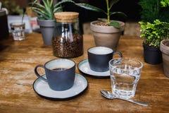 De koppen van koffie en het glas water op lijst in comfortabele koffie winkelen Stock Foto