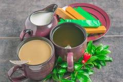 De koppen van koffie en thee, chocolade, kruik met melk en granaatappelboom vertakken zich met een bloem Stock Foto
