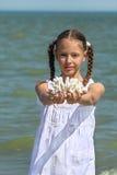 De koralen van de meisjesholding in zijn uitgestrekte handen Royalty-vrije Stock Foto's