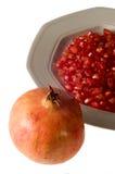 De korrels van de granaatappel op schotel met gehele granaatappel Stock Foto