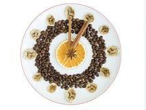 De korrels van geroosterde koffie, mokken van droge sinaasappel en banaan, pijpje kaneel, anijsplantster liggen op een porseleinp Royalty-vrije Stock Foto
