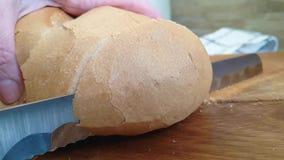 De korst van de broodbesnoeiing met een mes op houten stock video