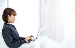 De korte haarvrouwen dragen zwarte overhemden Op een witte matras in de slaapkamer stock afbeeldingen