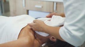 De kosmetiek arts die handdoek zetten aan gezicht van volwassen vrouwelijke klant stock videobeelden