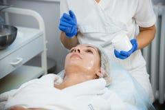 De kosmetiekprocedures schil Smerende room op het gezicht stock foto