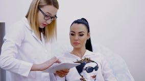 De de kosmetiekruimte, twee jonge mooie vrouwen, een arts en een patiënt bespreken diverse kosmetische procedures, bekijken stock footage