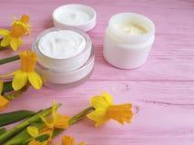 de kosmetische organische room van gele narcissennarcissen een roze houten uittreksel royalty-vrije stock afbeelding