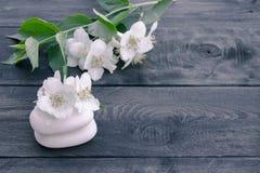 De kosmetische zeep en de witte jasmijnbloemen met groene bladeren liggen op een houten achtergrond Er is een plaats voor uw teks royalty-vrije stock foto