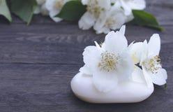 De kosmetische zeep en de witte jasmijnbloemen met groene bladeren liggen op een houten achtergrond Er is een plaats voor uw teks stock afbeeldingen