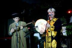 De kostuums die van Turkmeense Turkmenistan van de volksmuziekgroep nationale Oosterse mensen volksmuziek op volksinstrumenten sp Stock Afbeeldingen
