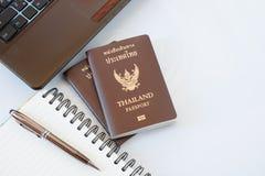 De kostuums van reistoebehoren Paspoorten Thailand, Voorbereiding voor reis, Notitieboekjepen op bovenkant, glazen, en laptop Stock Foto