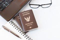 De kostuums van reistoebehoren Paspoorten Thailand, Voorbereiding voor reis, Notitieboekjepen op bovenkant, glazen, en laptop Royalty-vrije Stock Afbeeldingen