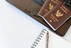 De kostuums van reistoebehoren Paspoorten Thailand, Voorbereiding voor reis, Notitieboekjepen op bovenkant, glazen, en laptop Stock Fotografie
