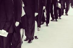 De kostuums wacht in lijn Retro zwart wit met toegevoegd lawaai royalty-vrije stock foto's