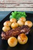 De koteletten van het lam met geroosterd aardappels en knoflook Stock Afbeeldingen