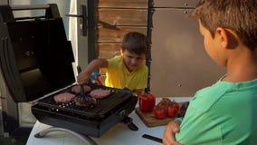 De koteletten van jongenskoks op de grill stock footage