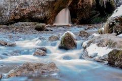 De koude bergrivier stroomt tussen stenen met sneeuw en ijs, selectieve nadruk, waterval op de achtergrond, lange blootstelling,  stock afbeelding