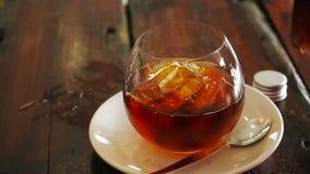 De koude brouwt koffie in een fles met hierboven ijsblokjes in een glastuimelschakelaar op een houten lijst van Een fles koude br stock video