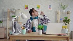 De koude jonge Aziatische mens in een overhemd gebruikt een nevel voor keelpijnzitting bij laptop stock videobeelden
