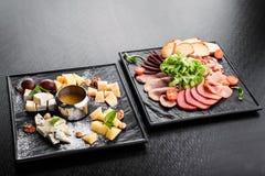 De koude rookte vleesplaat met varkenskoteletten, prosciutto, salami en broodstokken op een donkere achtergrond royalty-vrije stock foto