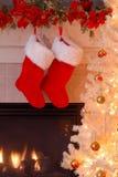De Kousen van Kerstmis door de Open haard Stock Foto