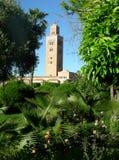 De Koutoubia-moskee van Marrakech door de groene vegetatie van het openbare park, Marocco stock fotografie