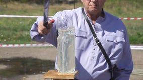 De kozak snijdt een plastic fles met water met een cavaleriesabel stock footage