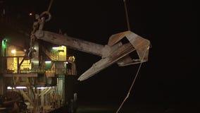 De kraan draagt een enorm anker van de boot aan het platform in de nacht stock video