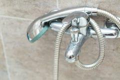 De kraan en de douche van Chrome in badkamers Stock Foto's