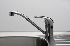 De kraan en de gootsteen van het water in grijs Stock Foto