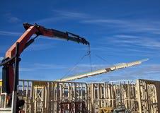 De kraan heft bundels in aanbouw op nieuwe huizen op Royalty-vrije Stock Foto's