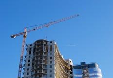 De kraan van de bouw op de achtergrond van een wolkenkrabber onder const Stock Afbeeldingen
