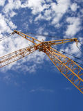 De kraan van de bouw tegen blauwe hemel stock afbeeldingen