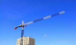 De kraan van de bouw tegen blauwe hemelachtergrond Royalty-vrije Stock Afbeeldingen