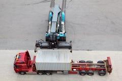 De kraan verplaatst en laadt container aan vrachtwagen Stock Fotografie