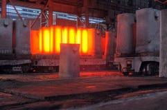 De kraan verwijdert vormen uit de verwarmde staalvarkens Royalty-vrije Stock Foto's