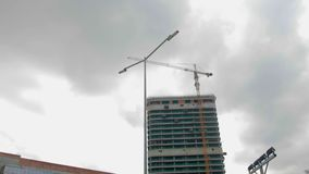 De kraan werkt aan de bouwwerf tegen de achtergrond van een high-rise gebouw stock video