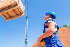 De kraanbestuurder levert een palletbakstenen bij bouw of de bouw Royalty-vrije Stock Foto
